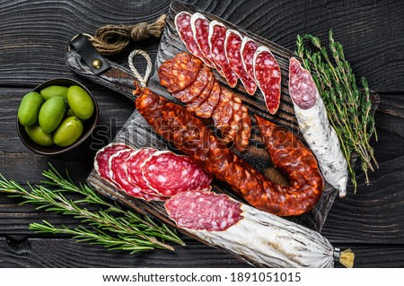 Spanish tapas sliced sausages salami, fuet and chorizo on a wooden cutting board. Black wooden background. Top view. Сток-фото ©