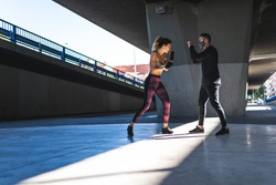 Spanish Woman Training Boxing with Coach Outdoors. Beautiful Woman Boxing with Personal Trainer. Personal Trainer Boxing. Sport concept.