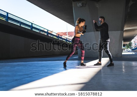 Spanish Woman Training Boxing with Coach Outdoors. Beautiful Woman Boxing with Personal Trainer. Personal Trainer Boxing. Sport concept. Stock fotó ©