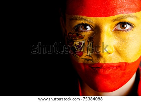 Spanish woman with the flag painted on her face ? isolated over a black background