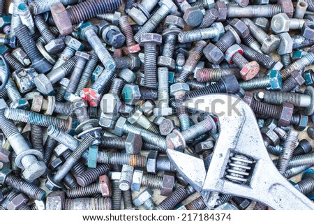 Spanner wrench and  screws on the wooden background