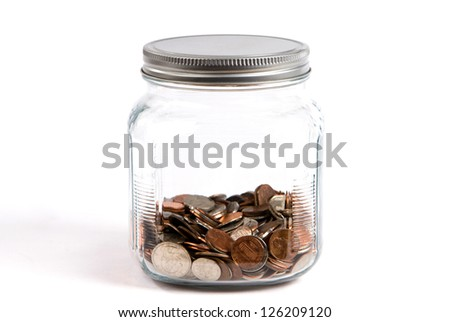 Spare change jar or piggybank holds coins in a glass container on white background.