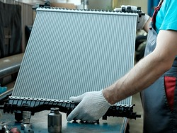 Spare parts for a passenger car.Radiator of the cooling system in close-up. An auto mechanic holds a new radiator in his hands.Repair and maintenance of the car in the service center.