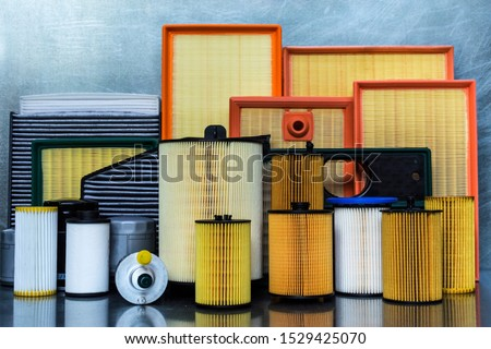 Spare parts for car. Oil filter, air filter, fuel filter, cabin filter close-up on a steel background.