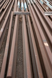 Spare railway track laying in dirt.  Parallel lines of track iron.  Rusty iron track in storage.  Brown, rusty iron.