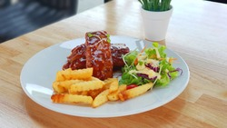 Spare ribs steak with green salad and frenchfries wooden table as background