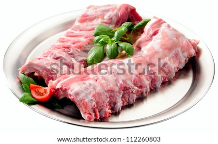 Spare ribs uncooked on stainless steel platter. Isolated on white.