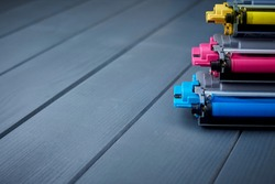 Spare toner cartridges for cyan, magenta and yellow color laser printer on gray wooden background
