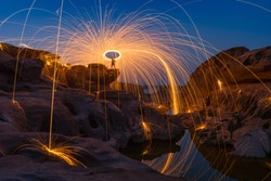 Spark fire swirl from steel wool over the rocks and reflection in water at night, Sam Phan Bok, Thailand.
