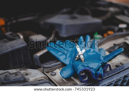 Spark plug. Car candles lie on gloves, in the background the engine