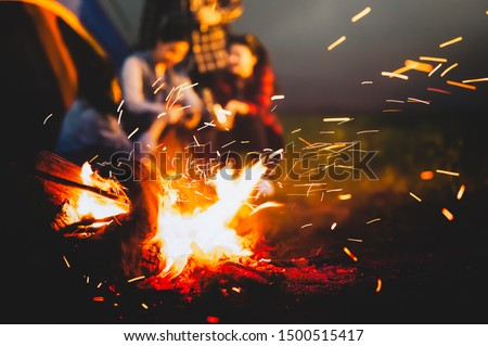 Sparking bonfire with tourist people sit around bright bonfire near camping tent in forest in summer night background. Group of student at outdoor fire fuel. Travel  activity and long vacation weekend
