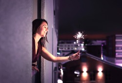 Sparkle in the night. Woman holding a sparkler out of window. New Year's Eve, Christmas party or birthday celebration at home. Happy elegant lady celebrating. City view. Light from firework stick.