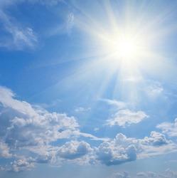 sparkle sun among dense cumulus clouds, natural summer sky background