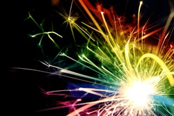 Sparkler background / A sparkler is a type of hand held firework that burns slowly while emitting colored flames, sparks, and other effects