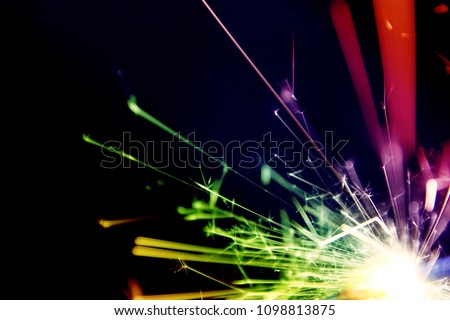 Sparkler background / A sparkler is a type of hand-held firework that burns slowly while emitting colored flames, sparks, and other effects  #1098813875