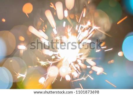 Sparkler Bokeh Colorful sparkler. Night background with a sparkler.  #1101873698
