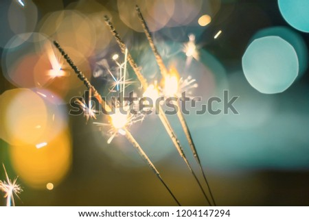 Sparkler Bokeh Colorful sparkler. Night background with a sparkler.  #1204147294