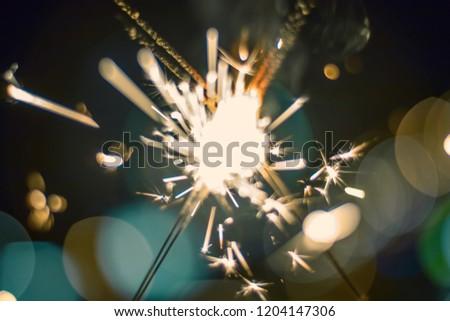 Sparkler Bokeh Colorful sparkler. Night background with a sparkler.  #1204147306