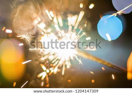 Sparkler Bokeh Colorful sparkler. Night background with a sparkler.  #1204147309