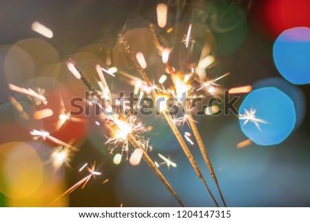 Sparkler Bokeh Colorful sparkler. Night background with a sparkler.  #1204147315