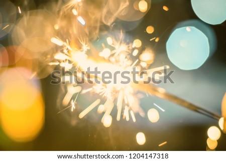 Sparkler Bokeh Colorful sparkler. Night background with a sparkler.  #1204147318