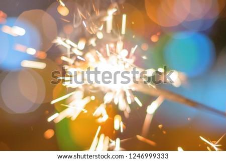 Sparkler Bokeh Colorful sparkler. Night background with a sparkler.  #1246999333
