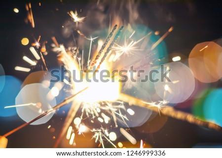 Sparkler Bokeh Colorful sparkler. Night background with a sparkler.  #1246999336