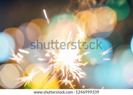 Sparkler Bokeh Colorful sparkler. Night background with a sparkler.  #1246999339