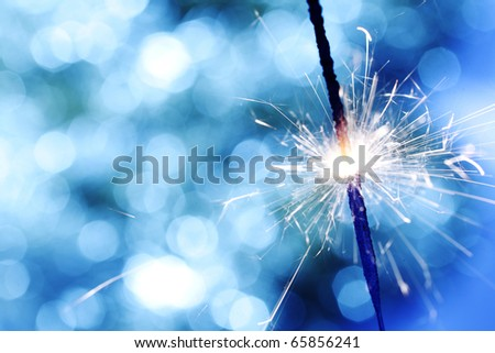 sparkler on blue bokeh background - stock photo