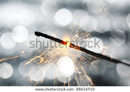 sparkler on silver bokeh background macro close up