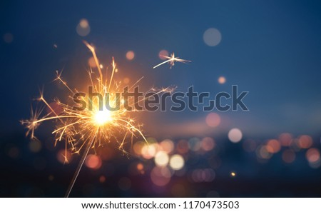 Sparkler with blurred busy city light background #1170473503