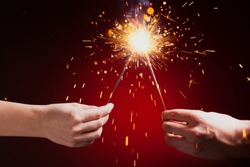 sparklers in hands, close-up view, red background