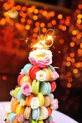 sparklers or burning candles on a birthday cake for the sixteenth birthday of macaroons and flowers close-up.