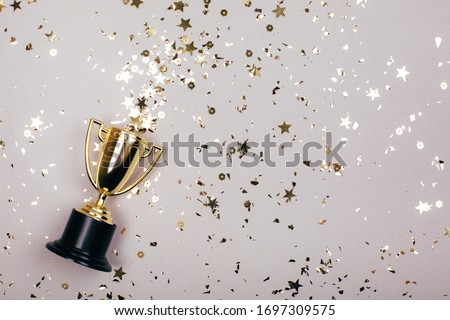 Sparkles grey background with a winners cup. Flat lay style.