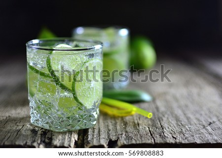 Sparkling cold water detox with lime and ice on a dark wooden background old #569808883