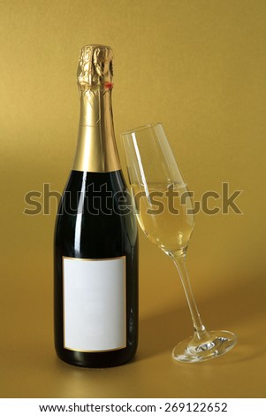 sparkling glass of champagne and bottle with blank label on golden background for jubilees