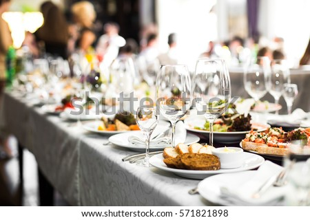 Sparkling glassware stands on long table prepared for wedding dinner