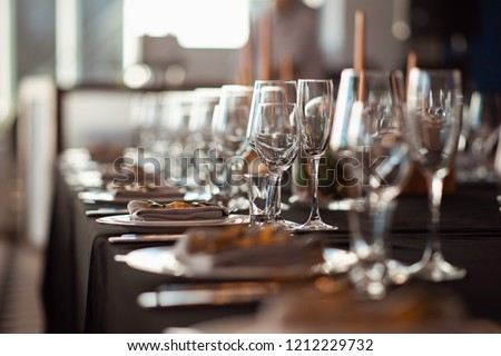 Sparkling glassware stands on table prepared for wedding. Wedding decor, interior. Festive. Banquet table.