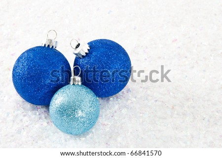 Sparkling glitter ornaments in shades of blue are clustered together on a frosty white snowy background