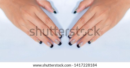 Sparkling Ivory Color Glitter Gel Polish Painting Black French Manicure on Beautiful Woman Fingernail  against White Background