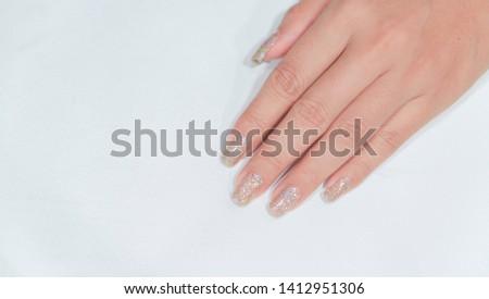 Sparkling Ivory Color Glitter Gel Polish Painting on Woman Fingernail against White Background
