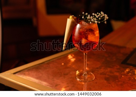 Sparkling light alcoholic cocktail with caramel popcorn, based on italian aperitif, apple cider, aperol and orange gin, served in blurred lights in a bar