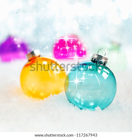 Sparkling twinkling colourful translucent glass Christmas baubles in fresh winter snow with bokeh of soft white lights, square format