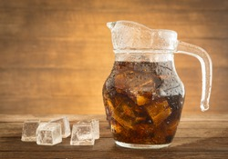 sparkling water in a jug with ice placed on a table of dark wood.