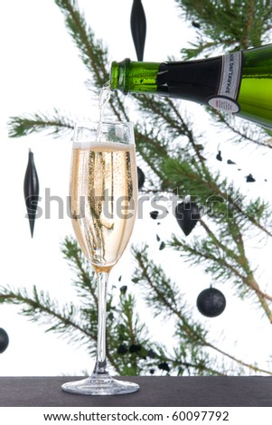 Sparkling wine poured into fluted champagne glass with christmas tree in background