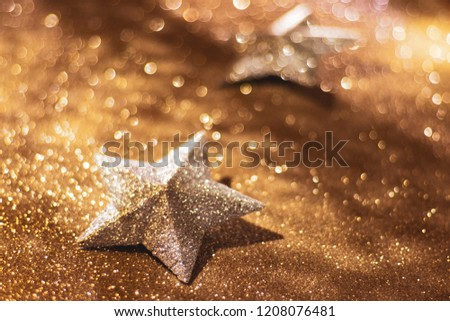 Sparkly gold stars on a sparkly gold glitter background (photograph)