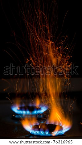 sparks and flames above gas stove burning with blue flames