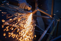 Sparks fly in all directions. Cutting metal with a grinder. Working in a metal workshop. Heating steel by friction. The flames of red-hot metal fly into the camera. Hand work in the garage.