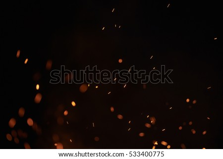 sparks from bonfire over dark night environment, shallow focus