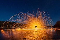 Sparks from the burning steel wool against the starry sky and the frozen river